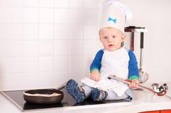 Weinig babychef-kok in de kokhoed met metaalgietlepel Royalty-vrije Stock Fotografie