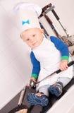 Weinig babychef-kok in de kokhoed met metaalgietlepel Royalty-vrije Stock Foto's
