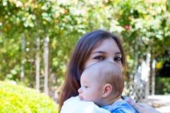 Weinig babyhoofd van profiel op de schouder van jonge moeder, mooi mamma met maakt omhoog op de ogen houdt baby stock afbeelding
