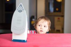 Weinig babyjongen bereikt aan heet ijzer stock afbeelding
