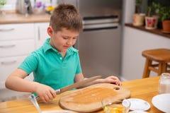 Weinig babyjongen bereikt keukenmes - gevaar in keuken stock fotografie
