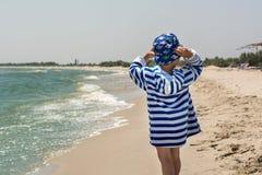 Weinig babyjongen bevindt zich met zijn achterholding Panama van de wind in een gestreepte robe op de kust Stock Afbeeldingen