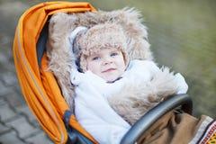 Weinig babyjongen in de warme winter kleedt openlucht Stock Afbeeldingen