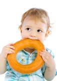 Weinig babyjongen die een ongezuurd broodje houdt Stock Foto
