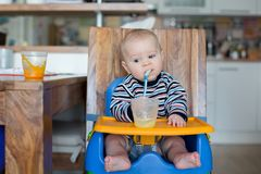 Weinig babyjongen, die fijngestampt voedsel voor het eerst eten stock afbeelding