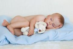 Weinig babyjongen, die met teddy stuk speelgoed slapen Stock Afbeelding
