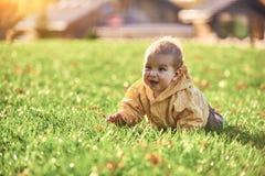 Weinig babyjongen die onder de gevallen bladeren op het groene gazon kruipen bij zonnige dag stock afbeeldingen
