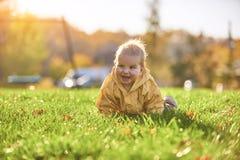Weinig babyjongen die onder de gevallen bladeren op het groene gazon kruipen bij zonnige dag royalty-vrije stock afbeeldingen