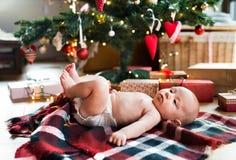 Weinig babyjongen die onder Kerstboom op gecontroleerde deken liggen Stock Foto's