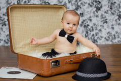 Weinig babyjongen in een koffer Stock Foto's
