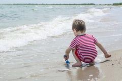 Weinig babyjongen ging zitten dichter aan het water en het spelen met zandschop op het strand Royalty-vrije Stock Afbeelding
