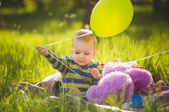 Weinig babyjongen het spelen speelgoed die op lang groen gras buiten zitten royalty-vrije stock afbeeldingen