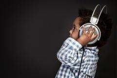 Weinig babyjongen in hoofdtelefoons stock foto