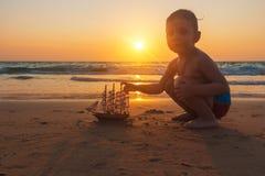 Weinig babyjongen speelt met stuk speelgoed schip op het zand van verbazend tropisch strand van Andaman-overzees in Thailand bij  royalty-vrije stock afbeeldingen