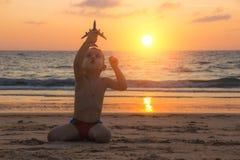 Weinig babyjongen speelt met stuk speelgoed vliegtuig op het zand van verbazend tropisch strand van Andaman-overzees in Thailand  stock afbeeldingen