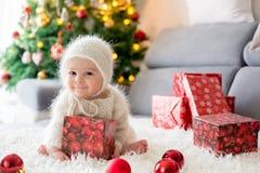 Weinig babyjongen in wit breide onesie, spelend met en openin royalty-vrije stock afbeelding