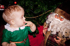 Weinig babyjongen zit onder verfraaide Kerstboom met Kerstman Royalty-vrije Stock Fotografie
