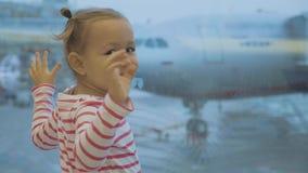 Weinig babymeisje bevindt zich naast venster bij luchthaven en golven in camera stock video