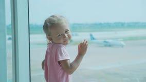 Weinig babymeisje bevindt zich naast venster bij luchthaven en het bekijken camera stock video