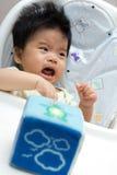 Weinig babymeisje dat op een hoge stoel schreeuwt Stock Foto