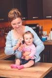 Weinig babymeisje die aan haar grootmoeder spreken Stock Foto's