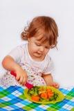 Weinig babymeisje die broccoli en wortel eten Stock Foto