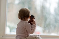 Weinig babymeisje die een stuk speelgoed koesteren die op de de wintersneeuw in openlucht letten stock fotografie