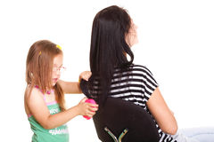 Weinig babymeisje die haar moedershaar borstelen Stock Fotografie