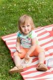 Weinig babymeisje die met blond haar lunch op het gras in het park eten Stock Foto