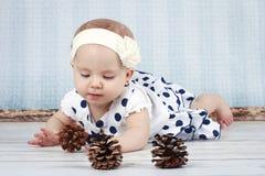 Weinig babymeisje die met kegels spelen Royalty-vrije Stock Afbeeldingen