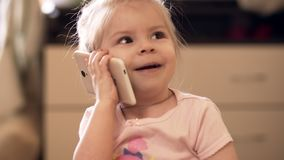 Weinig babymeisje die met telefoon binnen spelen UHD-schot stock videobeelden