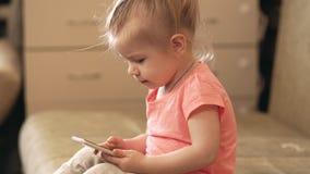 Weinig babymeisje die met telefoon thuis spelen 4k schot stock footage