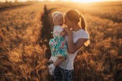 Weinig babymeisje en haar moeder die op het gebied lopen tickling Het glimlachen Zonsondergang Stock Fotografie