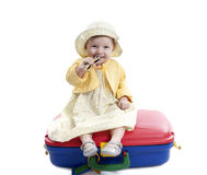 Weinig babymeisje gezet op rode en blauwe suitcas Stock Fotografie