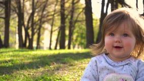 Weinig babymeisje in het park en het glimlachen stock videobeelden