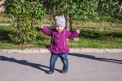 Weinig babymeisje in jeansjasje en hoed die het leren maken om zijn eerste stappen op het gazon in het groene gras te lopen Stock Foto's