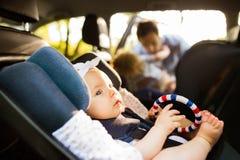 Weinig babymeisje maakte met veiligheidsriem vast in de zetel van de veiligheidsauto stock fotografie