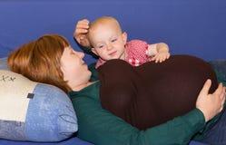 Weinig babymeisje met haar zwangere moeder Stock Foto's