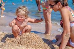 Weinig babymeisje met moeder op strand Royalty-vrije Stock Foto's