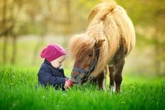 Weinig babymeisje met rode appel en poney Stock Fotografie