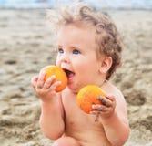 Weinig babymeisje met zoete sinaasappelfruit Stock Afbeelding