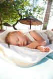 Weinig babymeisje in slaap op een chaise zitkamer Stock Afbeeldingen