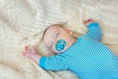 Weinig babyslaap Witte achtergrond met blauwe kleding uitsteeksel royalty-vrije stock afbeelding
