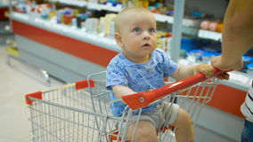 Weinig babyzitting in een kruidenierswinkelkar in een supermarkt, terwijl zijn vader aankopen kiest stock video