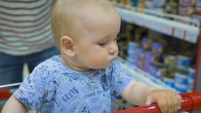 Weinig babyzitting in een kruidenierswinkelkar in een supermarkt, terwijl zijn vader aankopen kiest stock videobeelden