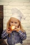 Weinig bakker Kind die broodbroodje op witte bakstenen muur eten royalty-vrije stock foto