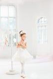Weinig ballerinameisje in een tutu Aanbiddelijk kind het dansen klassiek ballet in een witte studio royalty-vrije stock fotografie