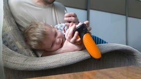 Weinig besmetting van het jongensoor vader bespuitende geneeskunde aan het oor van de jongen stock video