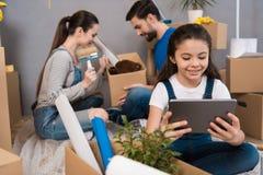 Weinig blij meisje wordt gespeeld in tablet terwijl de ouders huisreparatie doen stock afbeeldingen