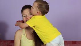 Weinig blije baby die en gelukkige moeder koesteren kussen stock footage